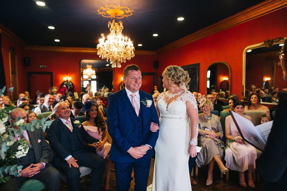 a bride looks back at her guests during the wedding ceremony as the groom looks ahead. cleveland tontine wedding teesside north yorkshire - relaxed and creative wedding photographer