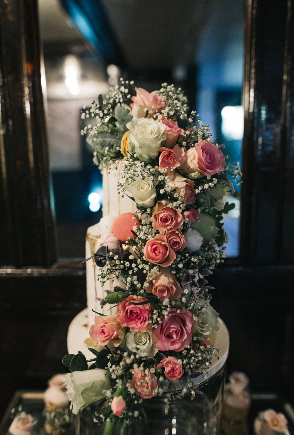 a shot of a tall two tier cake covered in pink roses. cleveland tontine wedding teesside north yorkshire - relaxed and creative wedding photographer