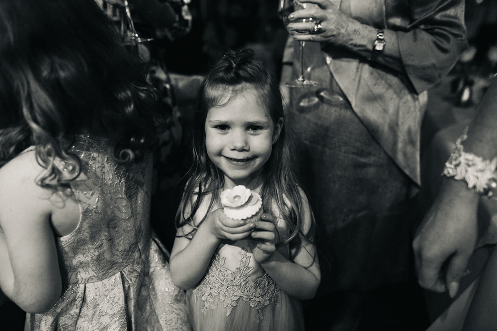 a young girls holds a cupcake and looks to the camera. cleveland tontine wedding teesside north yorkshire - relaxed and creative wedding photographer
