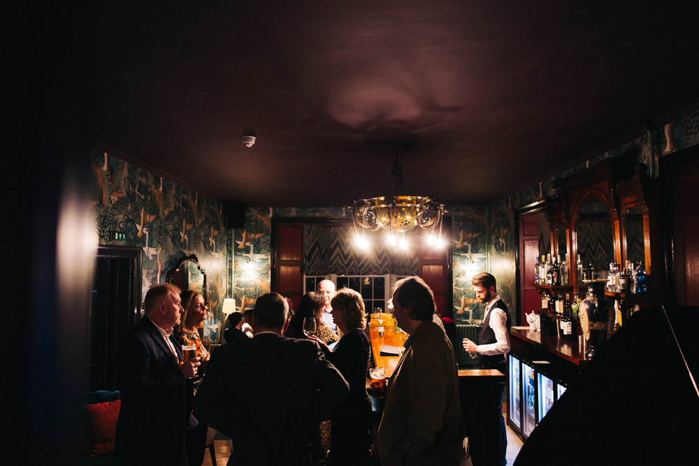 a wide shot of evening guests standing at the bar. cleveland tontine wedding teesside north yorkshire - relaxed and creative wedding photographer