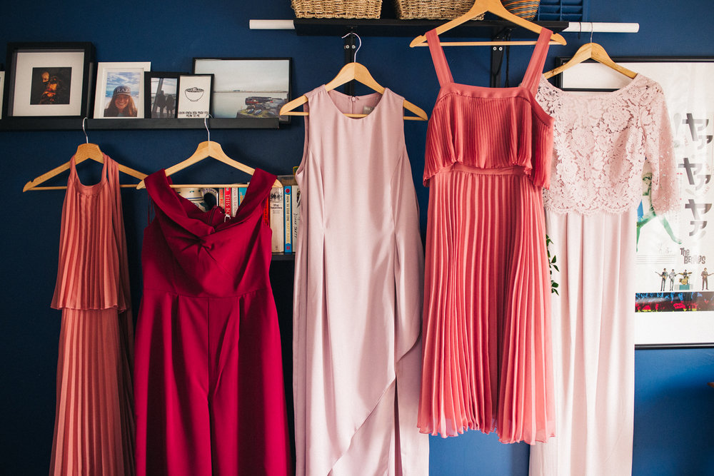 bridesmaids dresses are hung up - they are different shades of pink. ceremony at st georges hall liverpool, oh me oh my wedding reception, north west wedding photographer