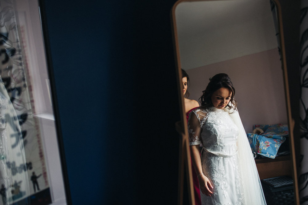 a relfection shot in the mirror of the bride being fastened into her dress. ceremony at st georges hall liverpool, oh me oh my wedding reception, north west wedding photographer