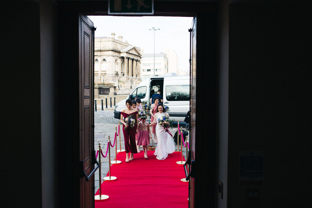 shot through the doorway of a bride arriving at the ceremony. ceremony at st georges hall liverpool, oh me oh my wedding reception, north west wedding photographer