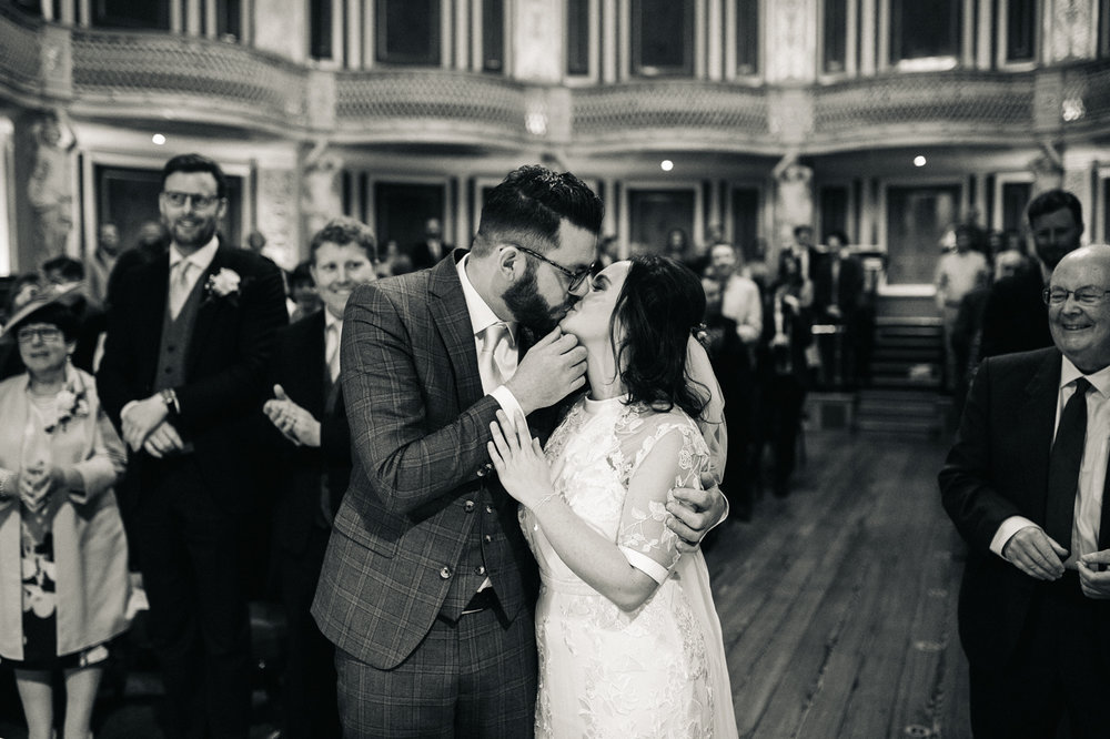 a black and white shot of the bride and groom kissing during the ceremony.ceremony at st georges hall liverpool, oh me oh my wedding reception, north west wedding photographer