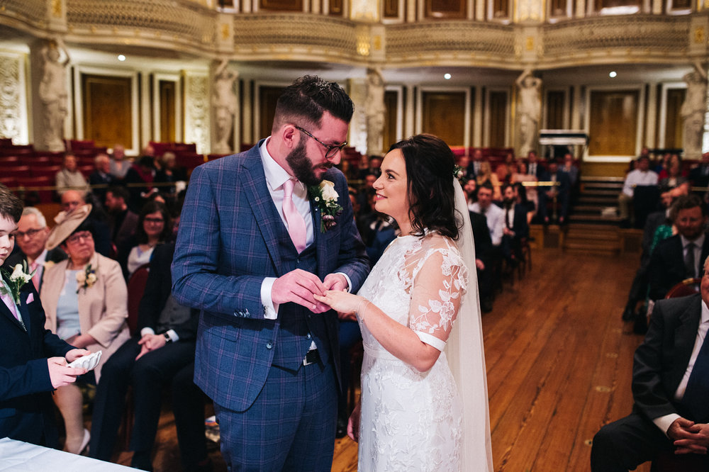 the exchange of rings. they smile at each other. ceremony at st georges hall liverpool, oh me oh my wedding reception, north west wedding photographer