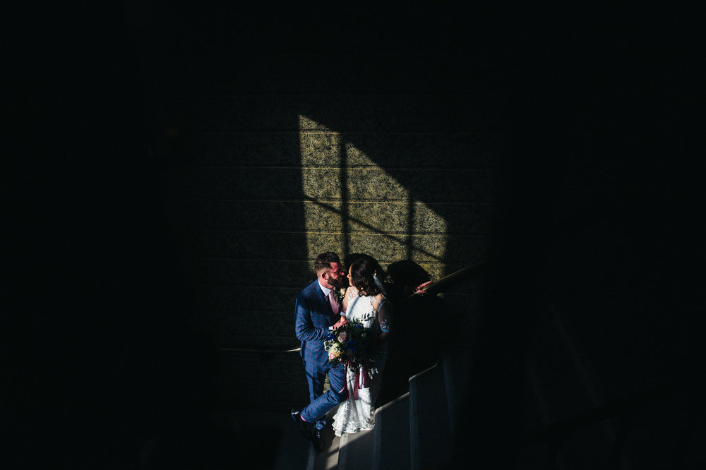 the bride and groom stand in a patch of light on the stairwell and kiss. ceremony at st georges hall liverpool, oh me oh my wedding reception, north west wedding photographer