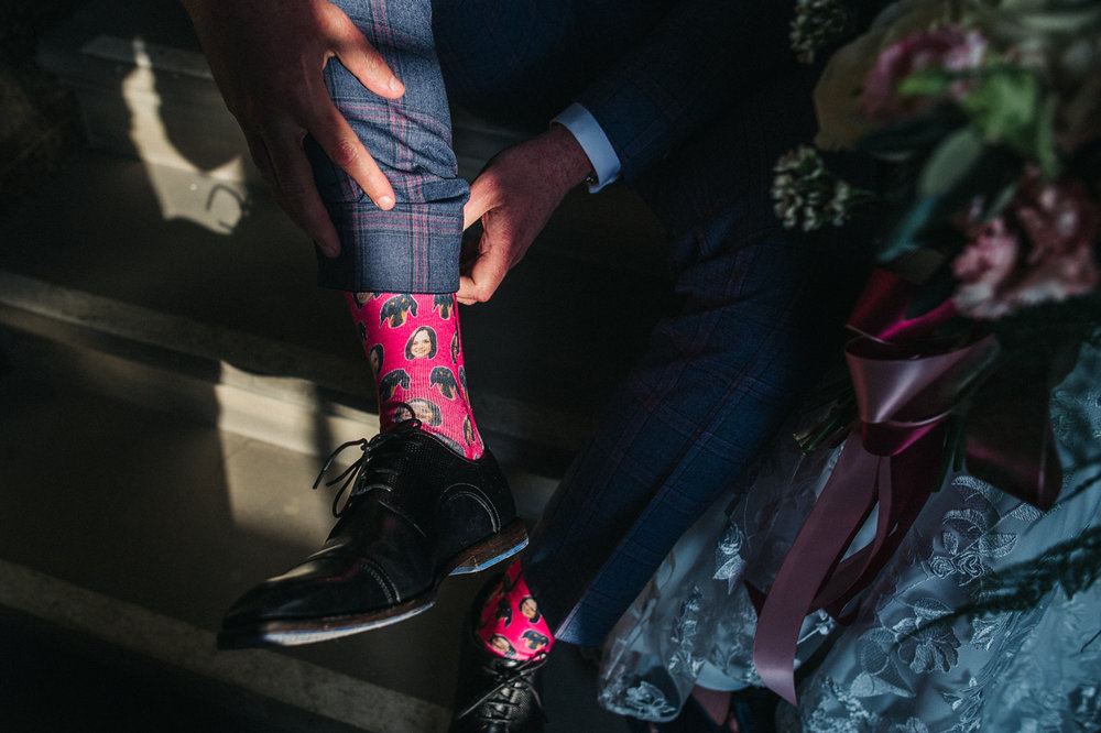 close up of the groom's socks which are fuscia and have the bride's face and their dog's face printed all over them. ceremony at st georges hall liverpool, oh me oh my wedding reception, north west