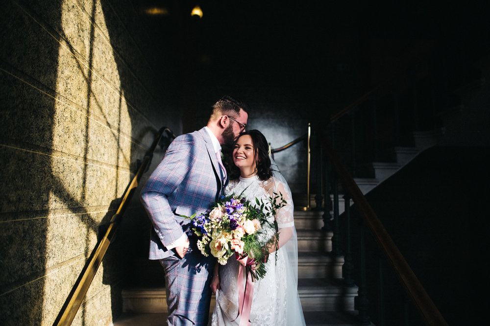 the bride and groom stand laughing on the steps. ceremony at st georges hall liverpool, oh me oh my wedding reception, north west wedding photographer