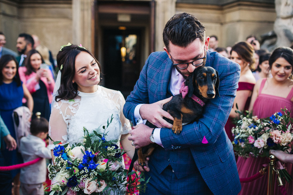 the bride and groom stand and hold their dog and cuddle it. ceremony at st georges hall liverpool, oh me oh my wedding reception, north west wedding photographer