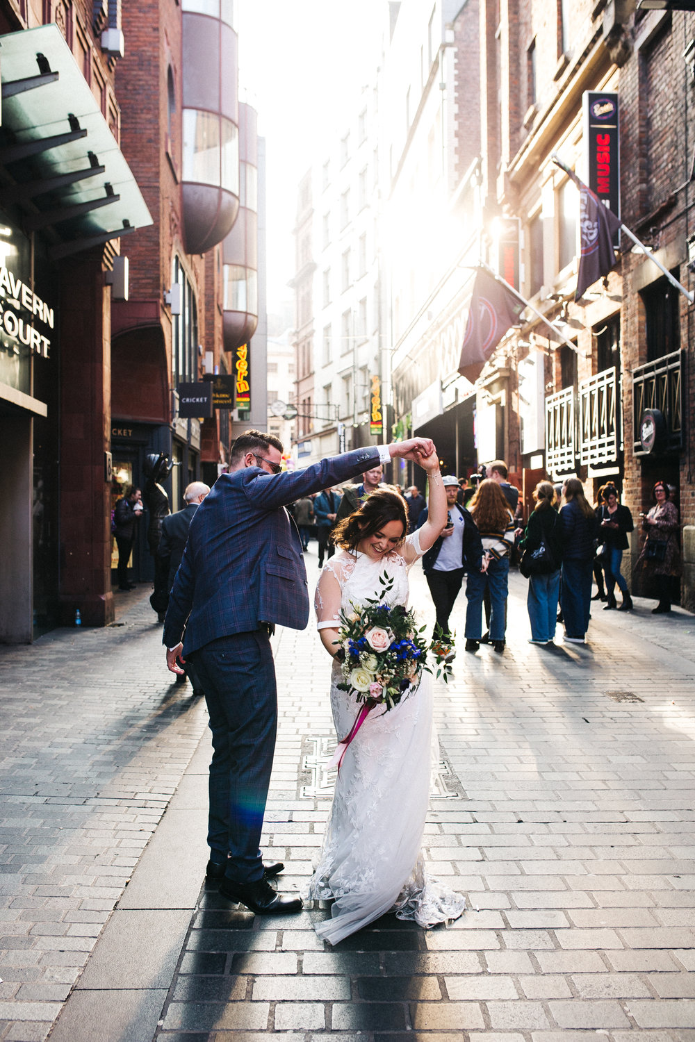 the groom twirls his bride on Matthew street in liverpool. ceremony at st georges hall liverpool, oh me oh my wedding reception, north west wedding photographer