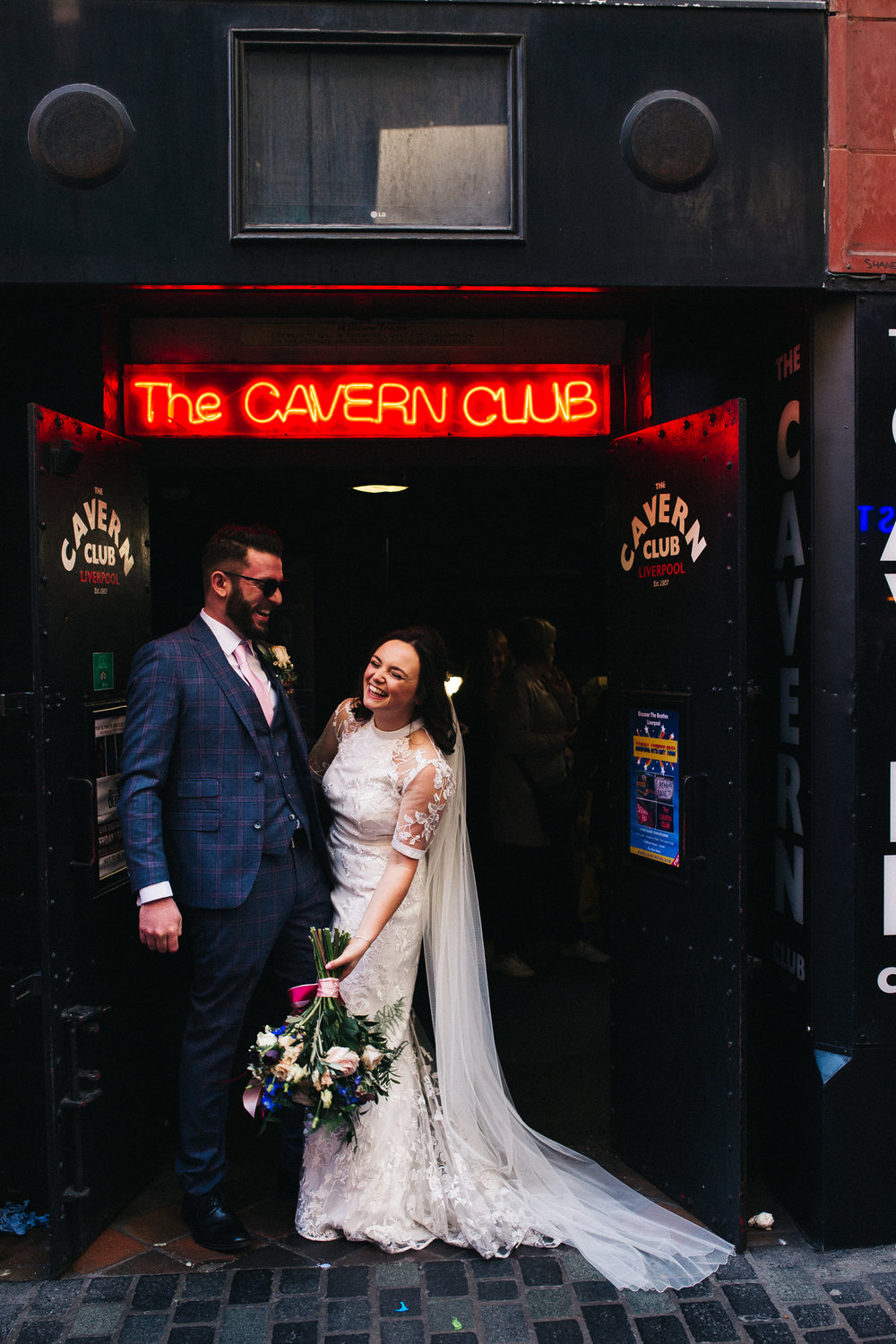 the bride and groom laugh together under the entrance to the cavern club in liverpool. ceremony at st georges hall liverpool, oh me oh my wedding reception, north west wedding photographer