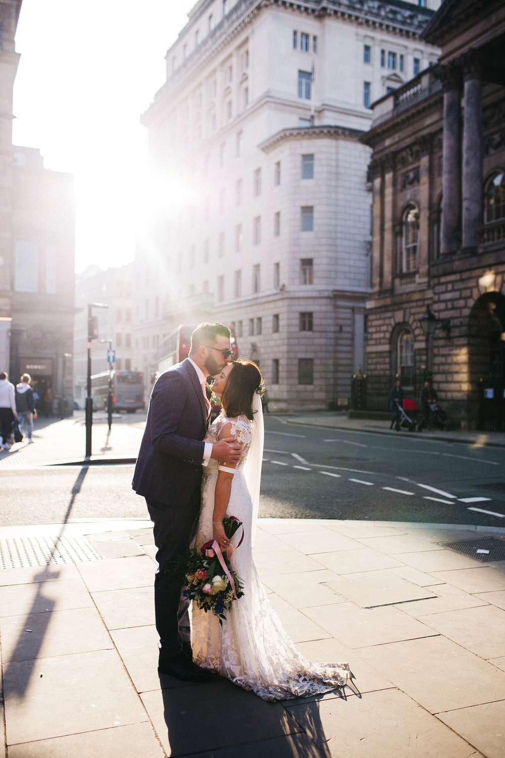 the bride and groom stand on the street and kiss - the light is beautiful. ceremony at st georges hall liverpool, oh me oh my wedding reception, north west wedding photographer