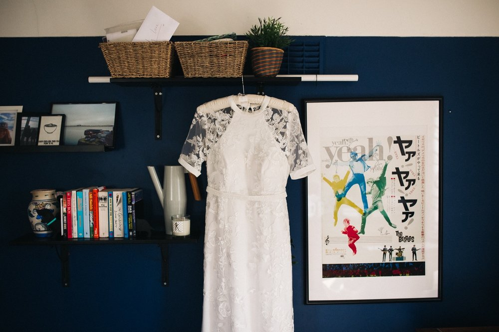 a wedding dress hangs on a navy wall. ceremony at st georges hall liverpool, oh me oh my wedding reception, north west wedding photographer