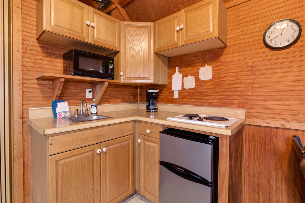The partial kitchen, featured here, includes a small refrigerator, two burner cooktop, microwave, sink, toaster, and coffee maker. Dishes, flatware, pots and pans, and glassware are also included.