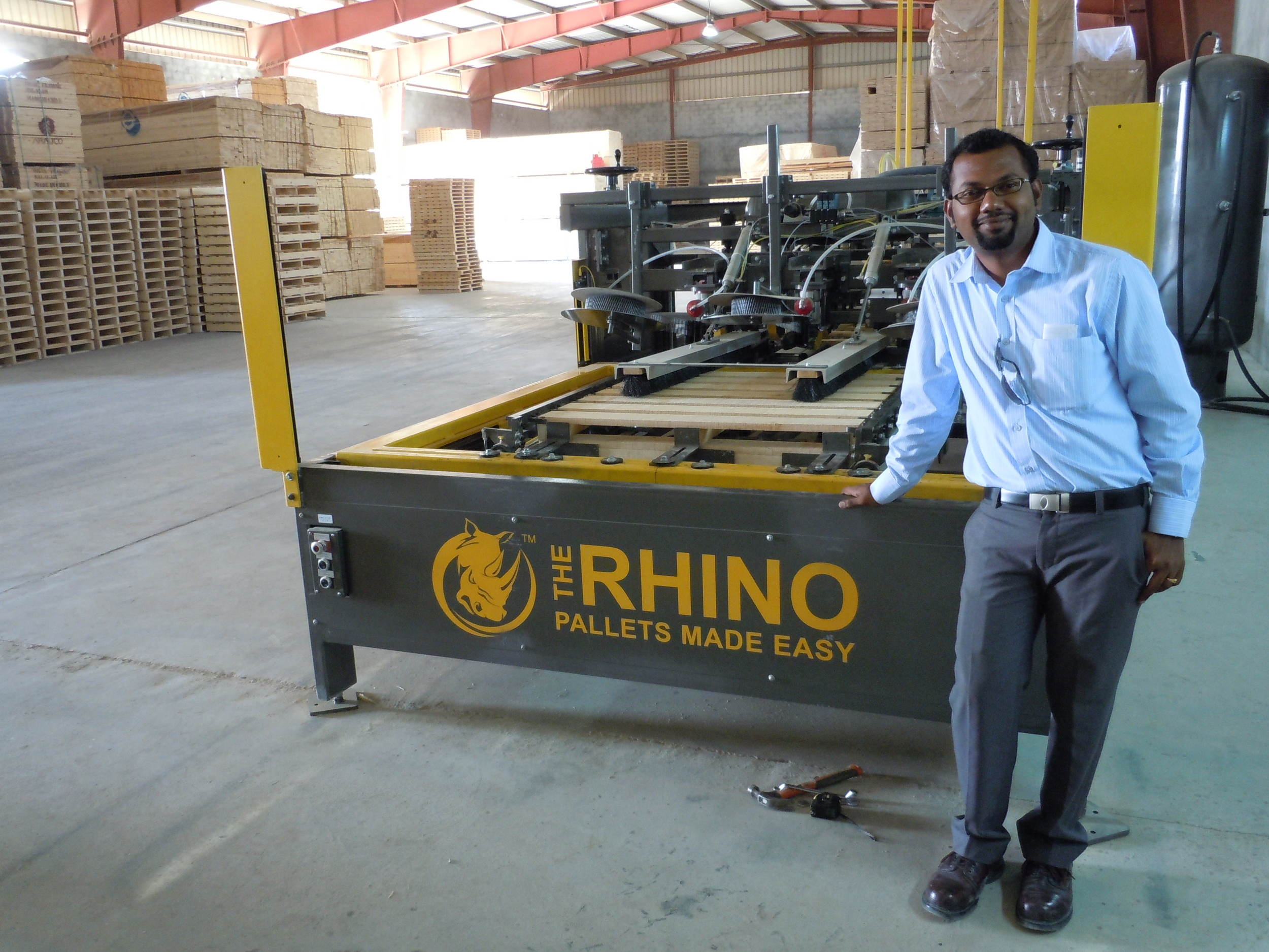 Head Engineer Jithin Madhoo from Omar Trading stands next to The Rhino Pallet Nailing Machine produce by BC Market Solutions.