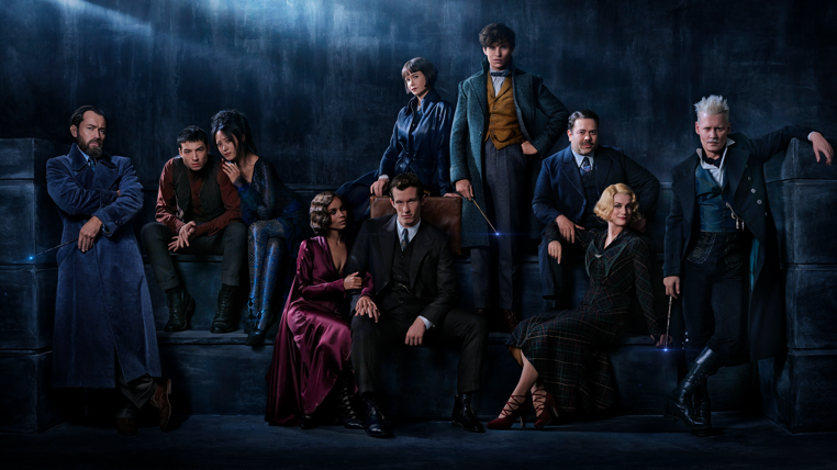 """(Left to right) JUDE LAW plays a young ALBUS DUMBLEDORE, taking on the mantle of one of J.K. Rowling's most beloved characters; EZRA MILLER makes a return as the enigmatic CREDENCE, whose fate was unknown at the end of the first film; CLAUDIA KIM appears as a Maledictus, the carrier of a blood curse that destines her ultimately to transform into a beast; ZOË KRAVITZ plays LETA LESTRANGE, who had once been close to Newt Scamander but is now engaged to his brother; CALLUM TURNER joins the cast as Newt's older brother, THESEUS SCAMANDER, a celebrated war hero and the Head of the Auror Office at the British Ministry of Magic; KATHERINE WATERSTON returns as TINA GOLDSTEIN, who has been reinstated as an Auror for MACUSA; EDDIE REDMAYNE stars again as wizarding world Magizoologist NEWT SCAMANDER, who has now gained fame in the wizarding world as the author of Fantastic Beasts and Where to Find Them; DAN FOGLER reprises the role of the only No-Maj in the group, JACOB KOWALSKI; ALISON SUDOL reprises the part of Tina's free-spirited sister, QUEENIE GOLDSTEIN, a Legilimens who can read minds; and JOHNNY DEPP returns as the powerful Dark wizard GELLERT GRINDELWALD in Warner Bros. Pictures' """"FANTASTIC BEASTS: THE CRIMES OF GRINDELWALD."""""""