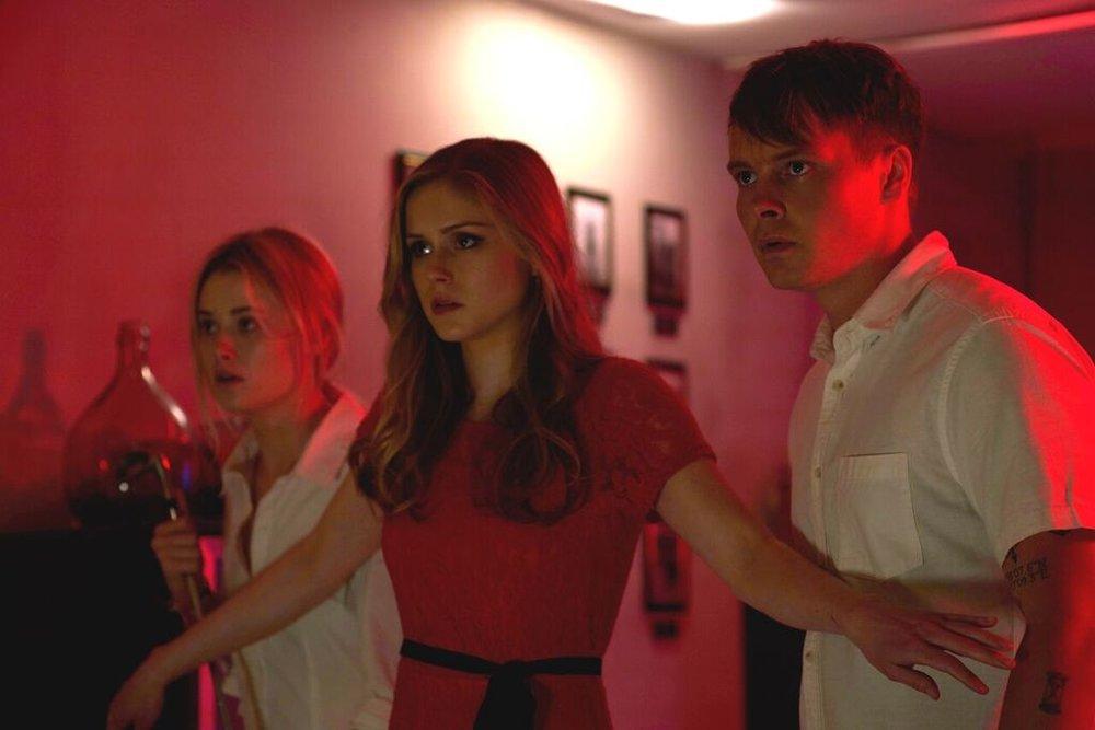 (L-R) Virginia Gardner as Iris, Erin Moriarty as Alexis, and Sam Strike as Casper in the horror/thriller film MONSTER PARTY, an RLJE Films release | Photo courtesy of RLJE Films