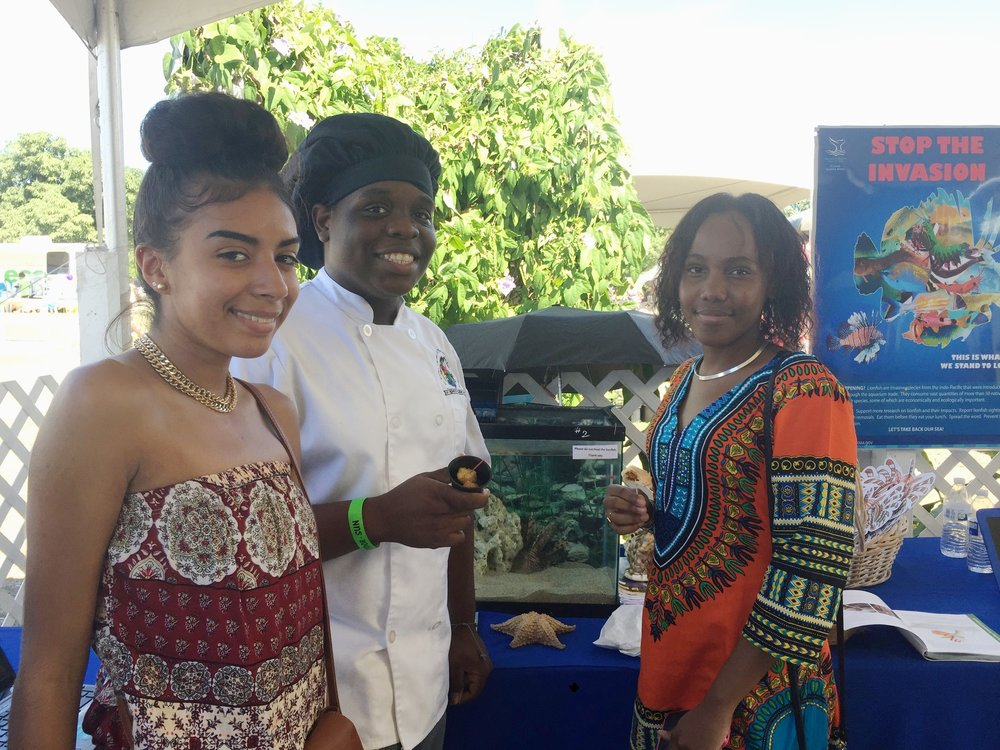 "As part of the ""Eat To Beat"" campaign, students affiliated with Virgin Islands Institute of STEM Education Research and Practice, University of the Virgin Islands and St. Croix Educational Complex promote the lionfish as a food source to help control the population. Some of the students are seen here for a public lionfish tasting event at the St. Croix annual Agricultural Fair"