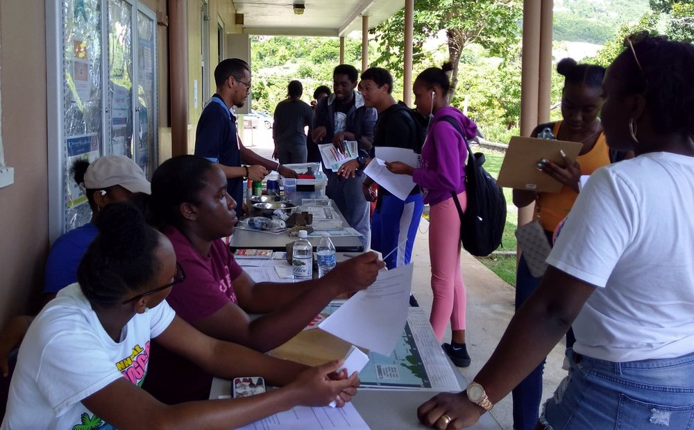 UVI students monitor and attend the Great ShakeOut global earthquake awareness event on the UVI campus, on October 18, 2018. Science 100 students helped write a quiz to test participants' knowledge of emergency preparedness, and they all assisted with educating attendees on disaster preparedness, including a review of the St. Thomas Recovery Team Emergency Preparedness Checklists and Worksheets (which they studied earlier this semester in class). Representatives from Virgin Islands Marine Advisory Service (VIMAS) and VI-EPSCoR ran demonstrations of preparedness tools such as water filters. Dr. Guannel guided students through the proper procedure for earthquake safety (drop, cover, hold on).