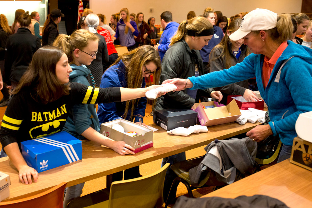 St,. Andrews Western coach Carla Wennberg hands a student a pair of socks to include in a package. Photo by Rooney Coffman