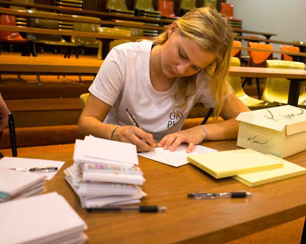 A student writes notes to soldiers. Photos by Rooney Coffman