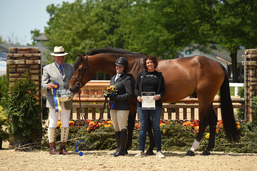 Melissa Hill of EquiFit presented a $100 gift certificate redeemable at Farm House Tack to Meagan Murray-Tenuta and Harvard, owned by Rebecca Price, champions of the 3' Green Hunters. Photo by Anne Gittins Photography