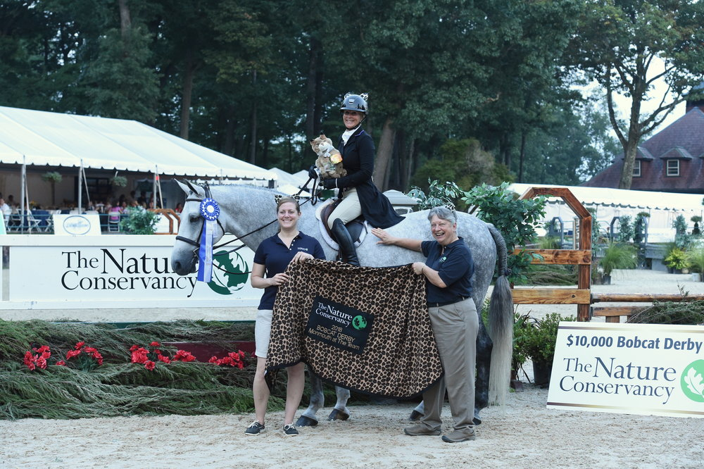 B.J. Ehrhardt and Micha 7:7 won the 3' section of the $10,000 Bobcat Derby, presented by The Nature Conservancy. Mary Conti and Barbara Brummer ,presented the award. Photo by Anne Gittins Photography