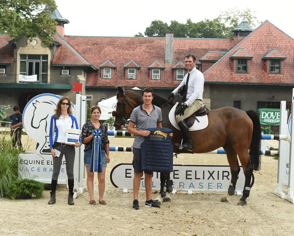 Elizabeth Ehrlich from Equine Elixirs presents a gift of Ulceraser. Niels Haesen and Maxime Tyteca from Stal de Eyckenhoeve present the Top Trip of the Day Award to Devin Ryan. Photo by Anne Gittins Photography