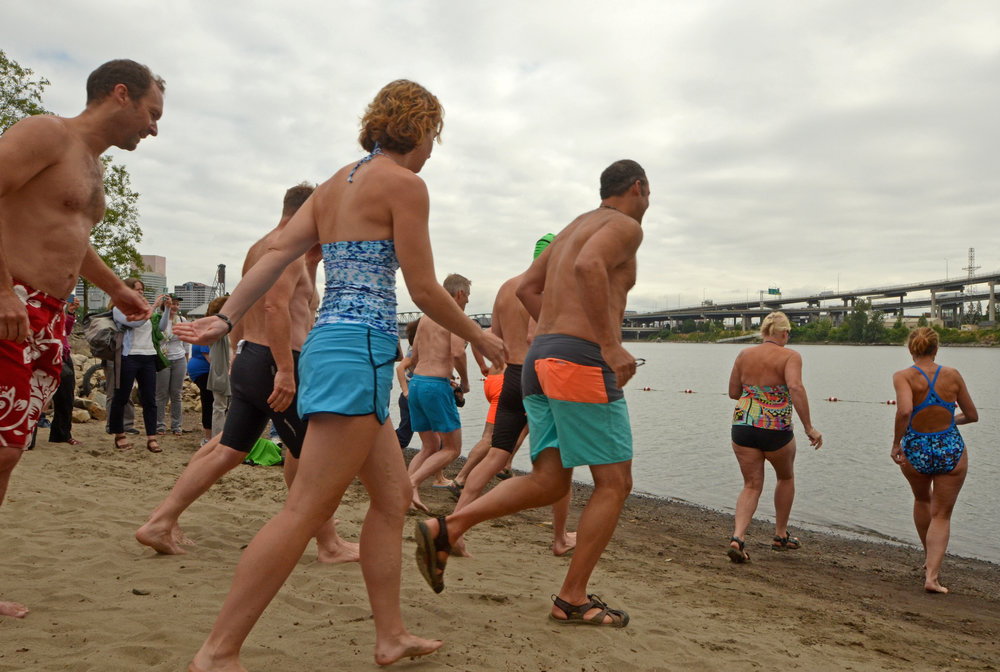 Folks run into the Willametter River for a swim at Poet's Beach's First Splash event July 13, 2017.