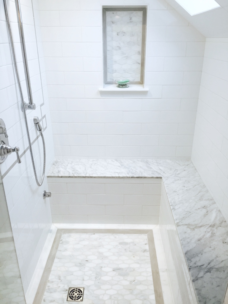 We designed this walk-in steam shower featuring heated marble slab seat, rainfall shower and custom tile inlays on floor and wall.
