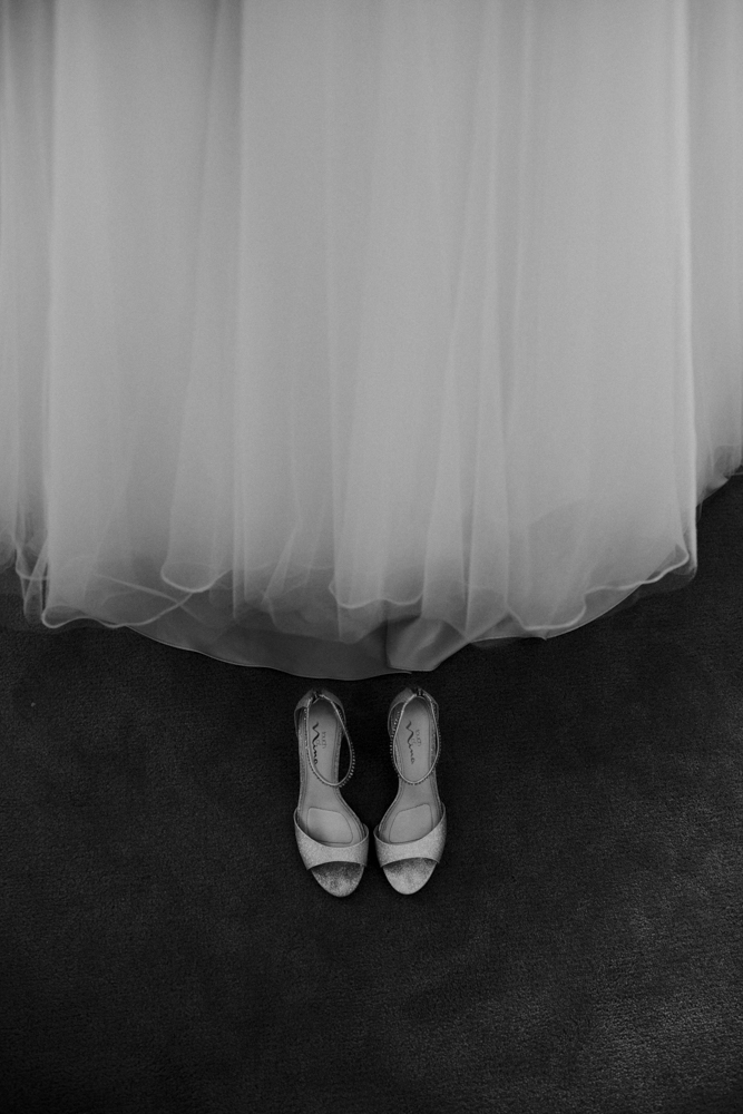 Detail of brides wedding dress and wedding shoes
