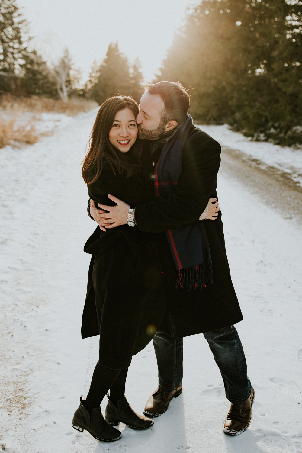 couple cuddling during winter engagement session at Bronte Creek Provincial Park