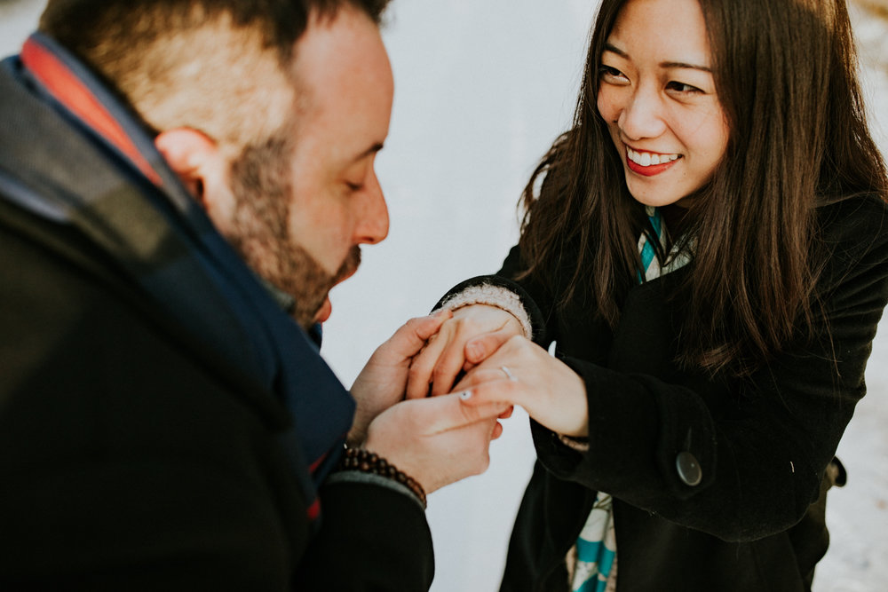 Cute couple showing engagement ring during winter adventure session
