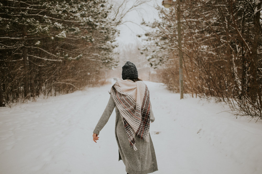Girl walking down snowy path in toronto