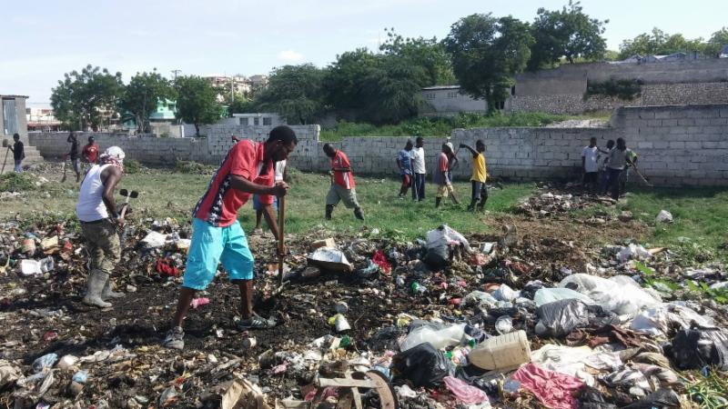 CLEAN UP   - community members join together fulfill their dream of a soccer field.