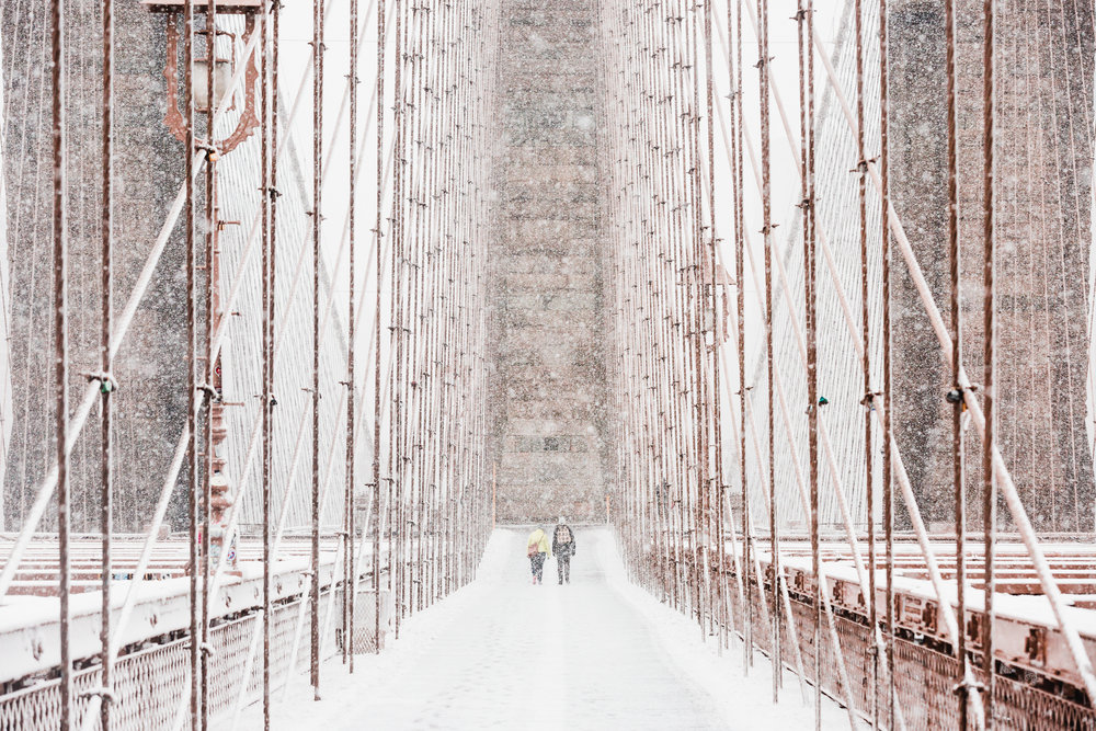brooklyn bridge people walking manhattan new york snowstorm tourist