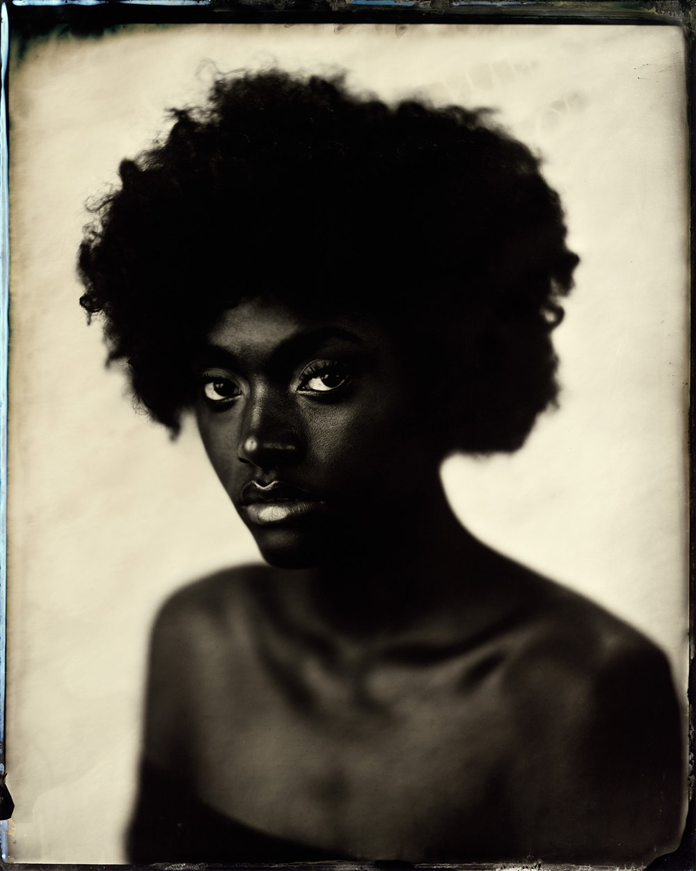 "Naomi on White - By: Ed Gately  ewgately.com   I have long been fascinated with the various ways the red pigmentation in our skin translates to collodion. Slightly under exposing skin tones can have dramatic effects. Pairing this with a high key background really shows off the the signature characteristics of the wet plate collodion process. Naomi was lit with 6' diffused parabolic umbrella and the background was lit with a zoom reflector from above. This 8x10"" tintype was captured with a Wollensak Vitax No. 5 on an E&HT Anthony 11x14"" Studio camera using hand mixed chemistry.  I am self-taught and creates my work following the traditions of the 19th century masters. Utilizing chemistry, light, and a little magic, my portraits are able to capture the soul of the sitter preserving them for many generations. In an age of photoshop and manipulation, my images force us to face who we are and to graciously accept it. In addition to portraits, my landscape work connects the present to the past in vivid detail."