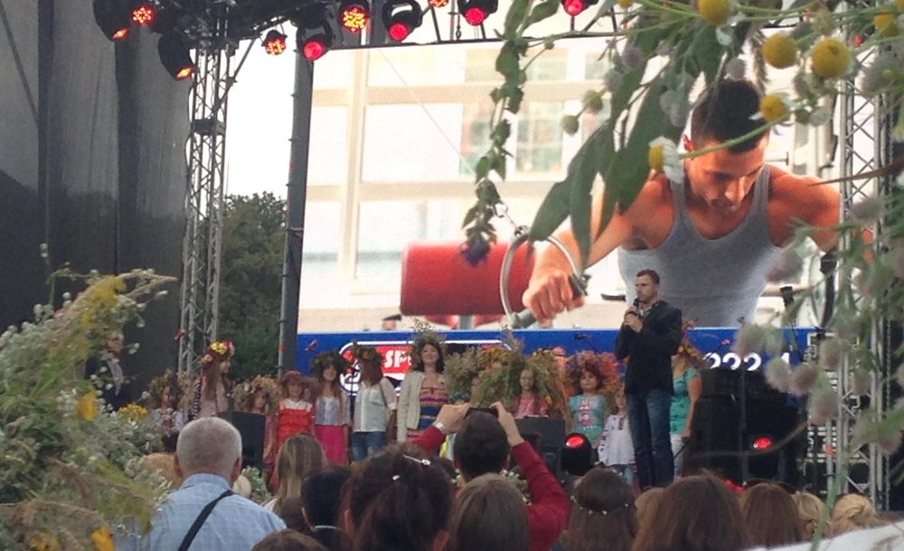 A contest for the best flower wreath at the Ukrainian folk solstice celebration, Ivano Kupala. I am assuming that the advertisements on the giant screen made the event financially possible. Note the winner of the contest, whose crown was so large it blocked other contestants from view.