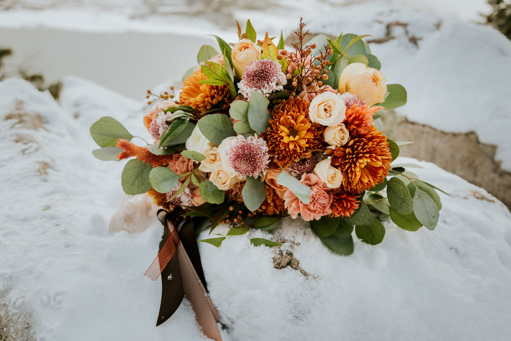 Jami and Eric's elopement at Sapphire Point on November 3, 2018 was a chilly winter wedding with another stunning bouquets. My favorite part of their wedding was the colors. I loved the green trees, the blue mountain and the pop her bouquet had with her orange shawl. Such a gorgeous day and bouquet by Pink Posey Design. -