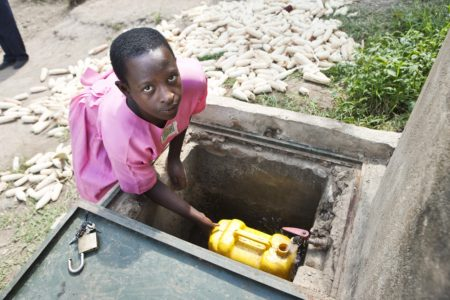 Frances draws clean water from a Brick by Brick rainwater harvesting tank