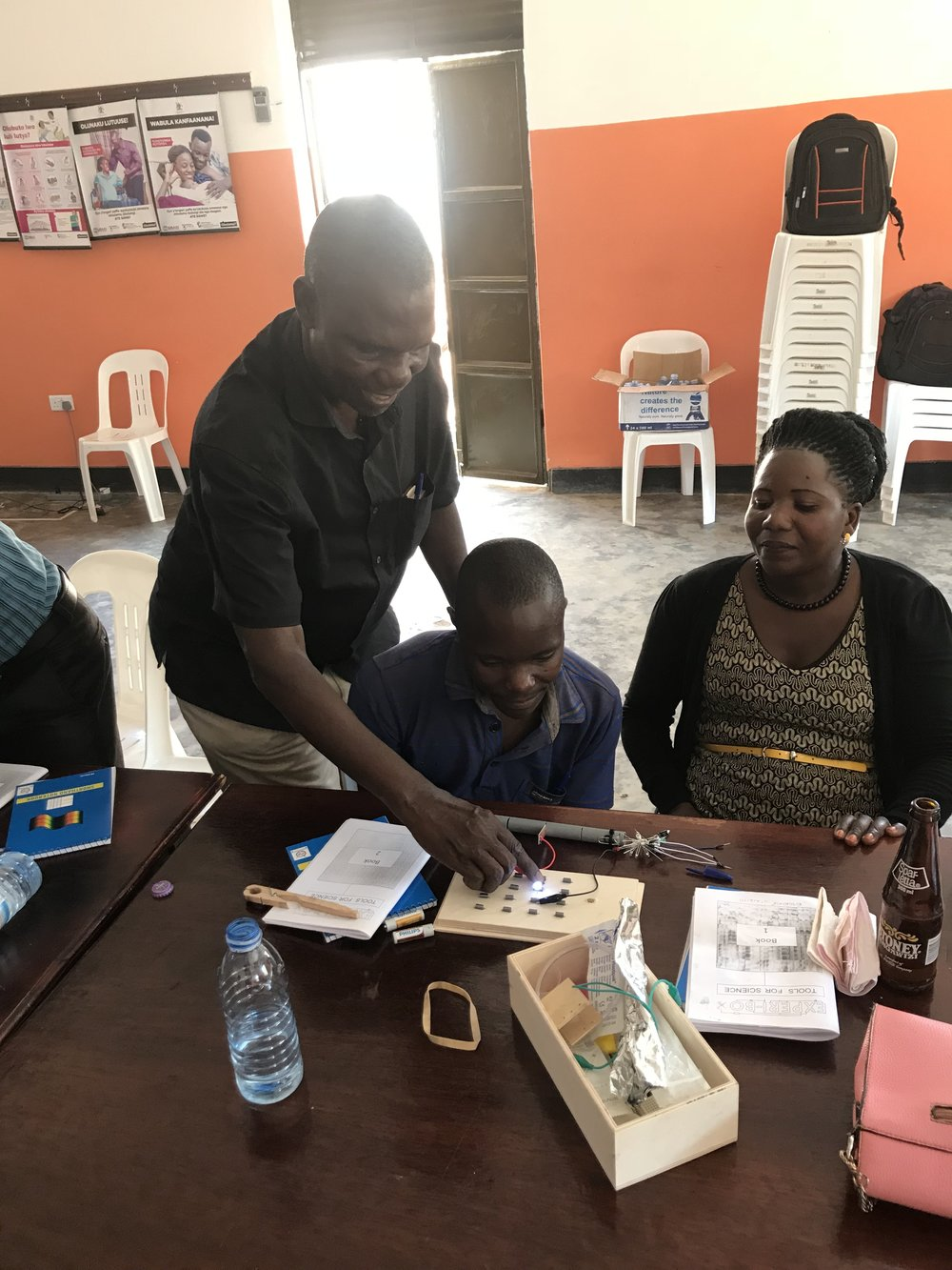 School Program Coordinator Max Ssenyonga Works with teachers using the Experi-Box to show how electric circuits works.