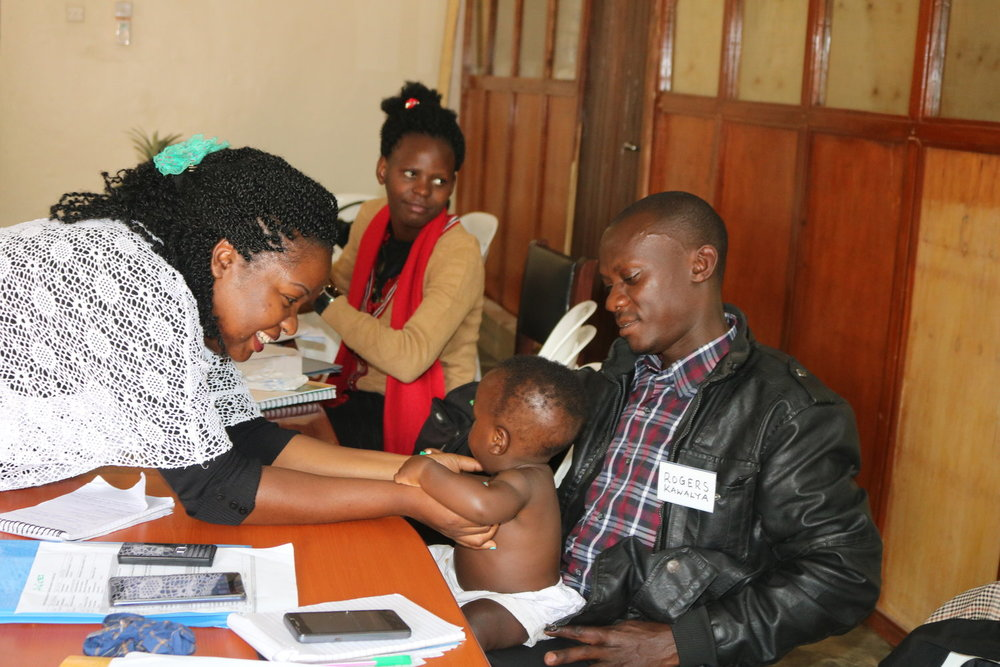 Dr Eleanor Nakintu, BAMA Program Clinical Director with a Papa Ambassador and his baby
