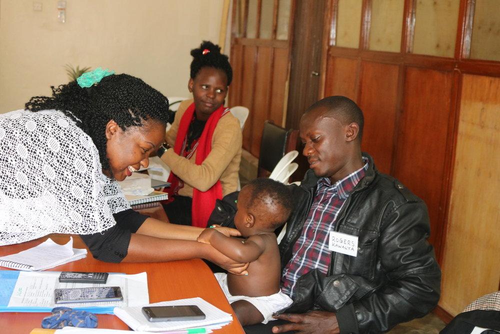 Dr Eleanor Nakintu, BAMA Program Clinical Director with a Papa Ambassador and his baby