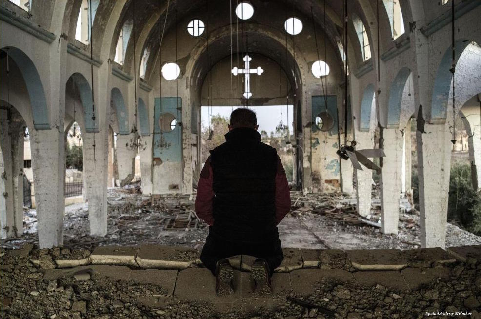 A resident of one of the Christian villages in Al-Hasakah province of Syria prays in the ruins of St. George's Church destroyed by ISIS militants. (Sputnik/Valeriy Melnikov)