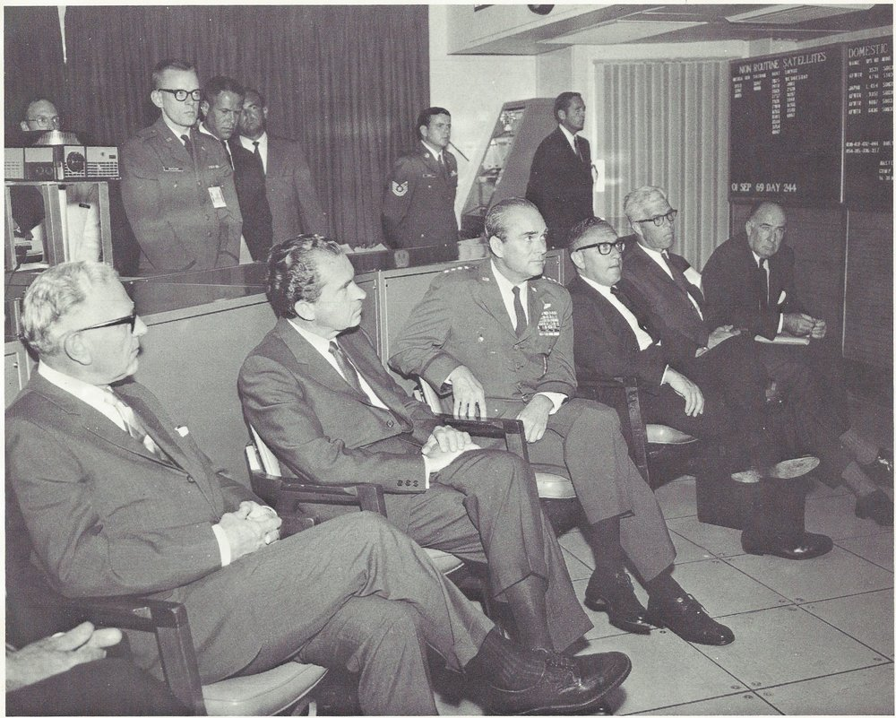 "Caption: ""DISTINGUISHED VISITORS - Richard M. Nixon is September 1969 became the first U.S. President to visit the underground command post of the North American Air Defense Command. He is shown here in NORAD's Space Defense Center being briefed by General Seth J. McKee, commander in chief of NORAD. Left to right are: Gordon Allott, U.S. Senator from Colorado; President Nixon; General McKee; Dr. Henry A. Kissinger, Presidential assistant; Peter H. Dominick, U.S. Senator from Colorado; and John N. Mitchell, U.S. Attorney General."""