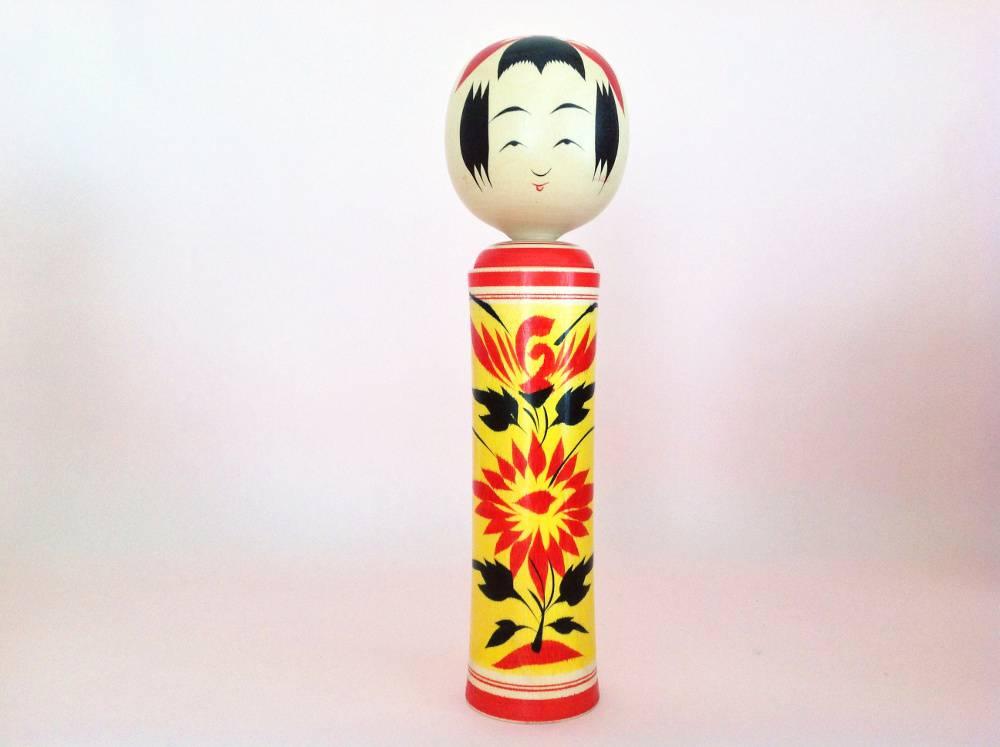 Kokeshi Naruko avec motif de chrysanthèmes sur fond jaune.