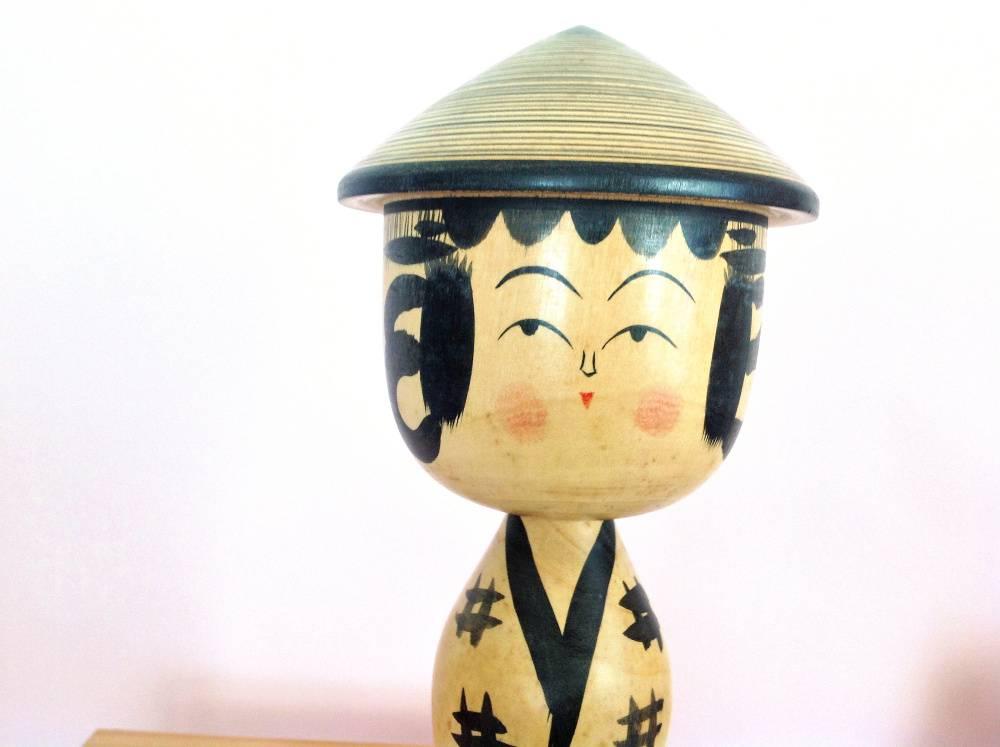 Poupée kokeshi Yajiro à chapeau, en noir et gris. Blush sur les joues, festons sur le front + cheveux qui dépassent sur les côtés, petit nez à trois traits.