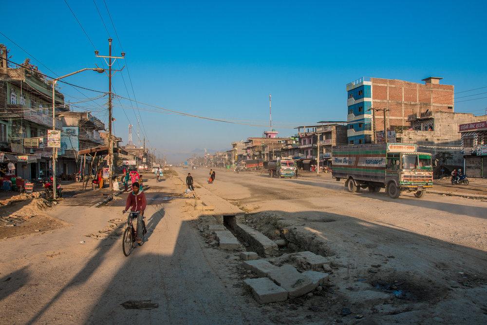 Pääkatu jossain Chitwanissa - horisontissa näkyy autojen nostamaa pölypilveä.