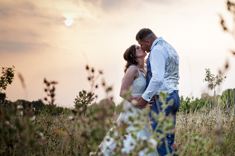 Lauren & Andy kiss under a sunset at Maidens Barn in Essex.