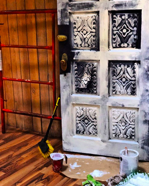 A close up photo of a white painted door and brown wooden porch with scaffolding and painting supplies laying about.
